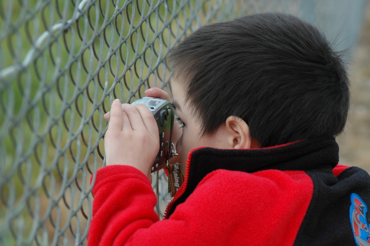 Michael composes a shot through the fence