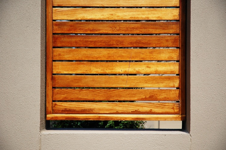 Wooden slats cover a gap in a concrete fence