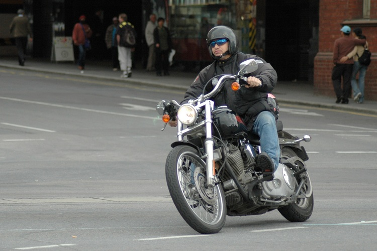 A guy on a motorcycle, in the city