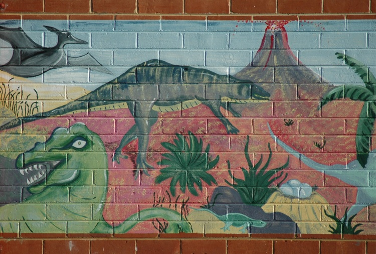 A dinosaur mural on a brick wall