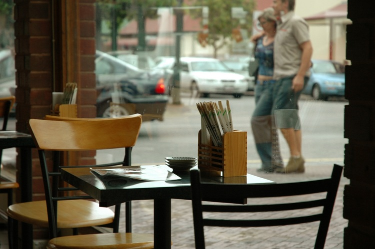A view into the street, past an empty table