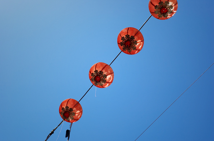 Red paper lanterns against a blue sky