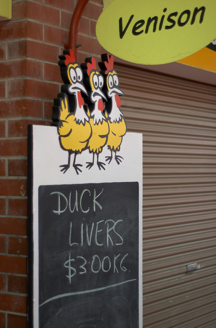 Sign reading 'Duck Livers', with a 'Venison' sign above it