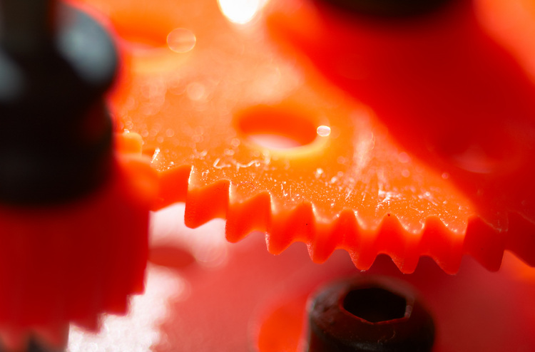 Bright orange Meccano cogs
