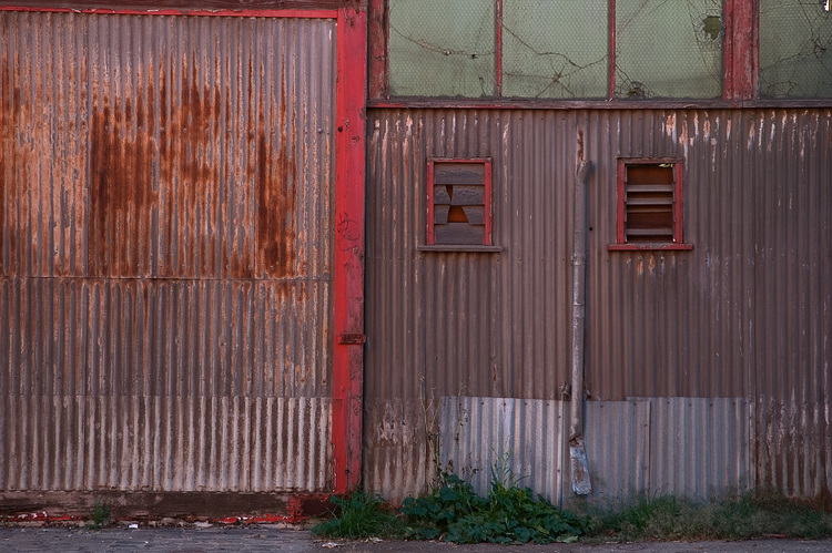 A rusty shed door with peeling red paint