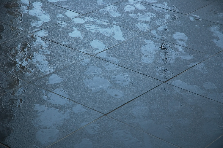 Footprints on lightly drizzled-on pavement