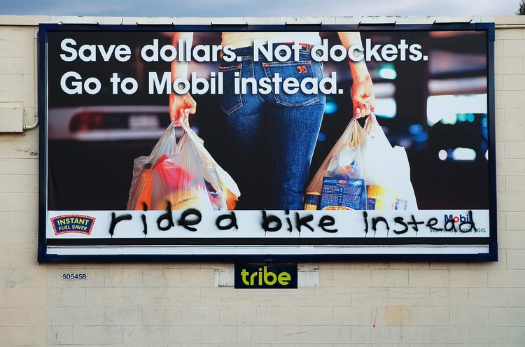 'ride a bike instead' graffitied across a billboard