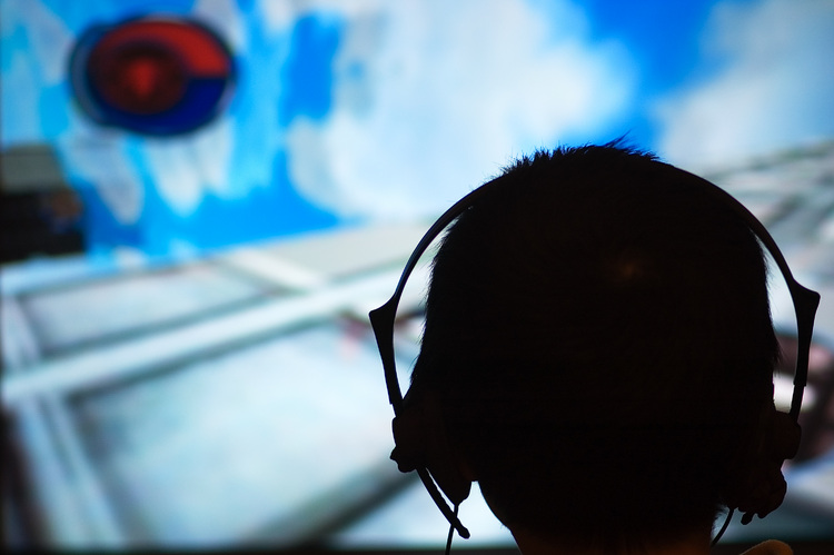 The silhouette of a head (wearing headphones), against a a TV screen