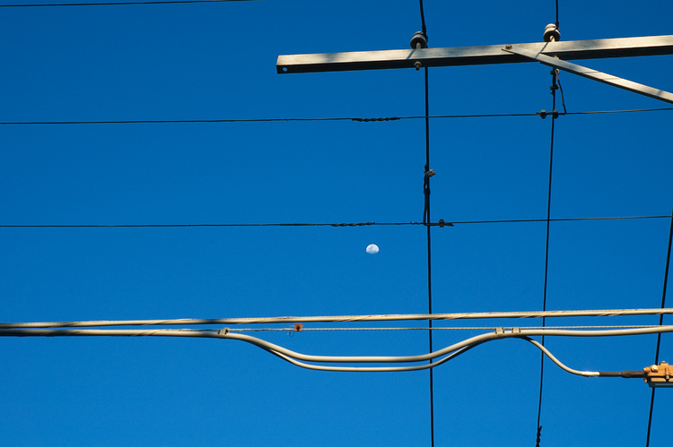 Utility wires, against a blue sky and the moon