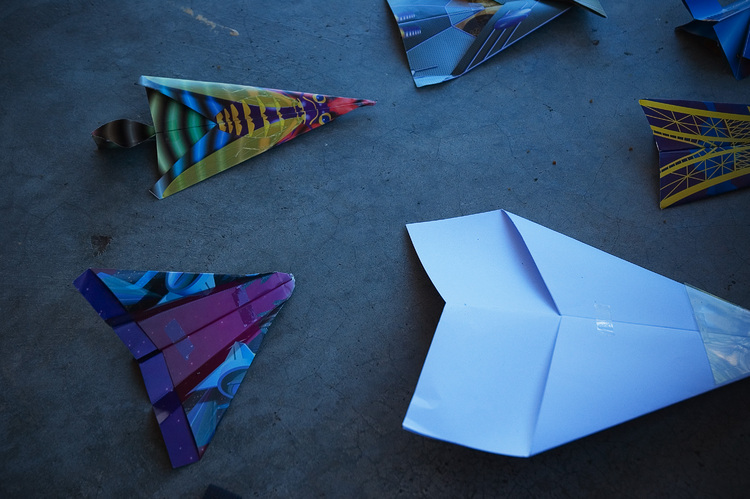 An array of paper planes, lying on the ground