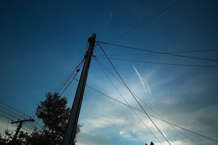 Jet contrails in the dusk sky, seen past a mess of wires