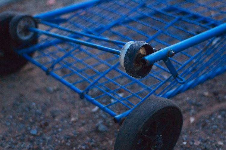 A blue cart, abandoned by the side of the road