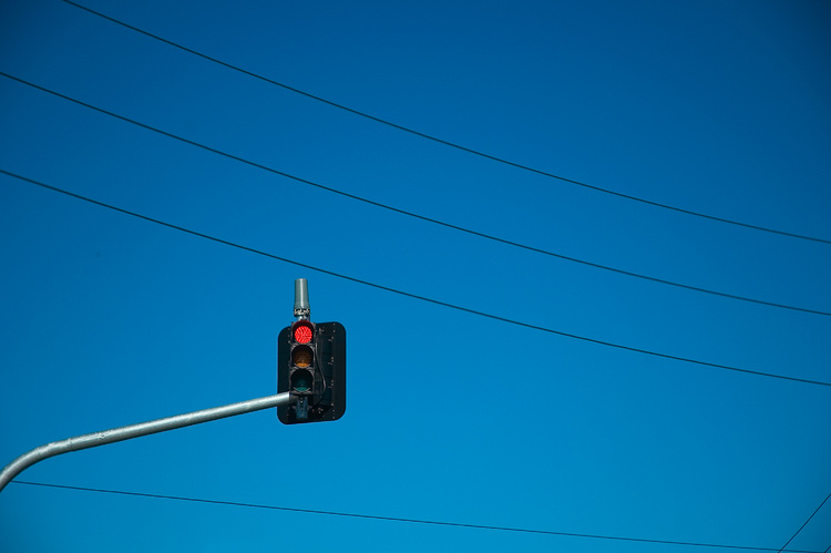 An overhead traffic light, surrounded by power lines