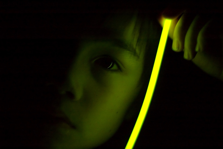 Michael holding a glow-stick next to his face