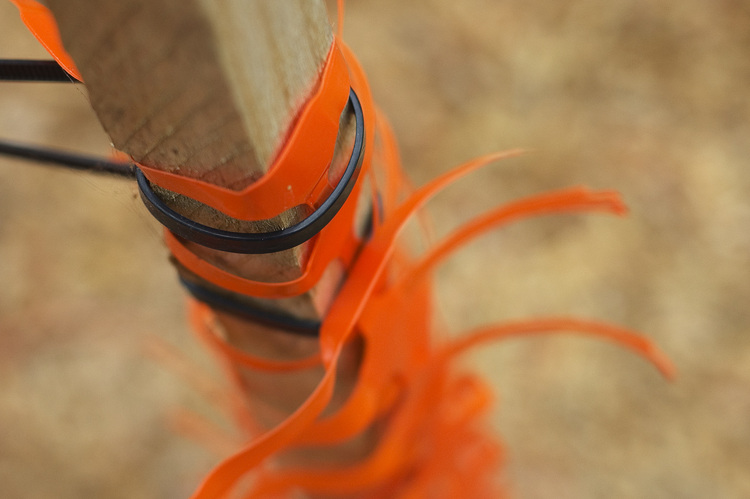 Orange safety netting tied to a post with black nylon ties