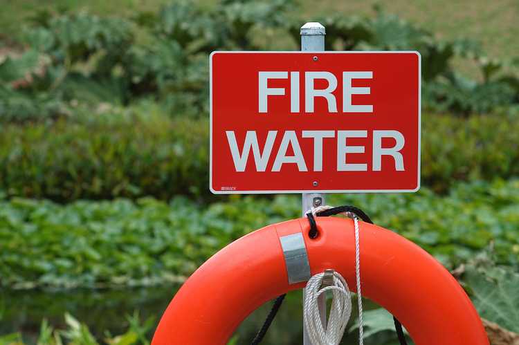 A life buoy, below a sign reading 'fire water'