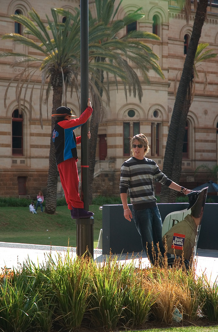 Michael hanging from a pole, chating to a guy on a Segway