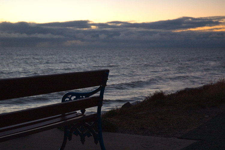 An empty bench, looking out over the sea at dusk