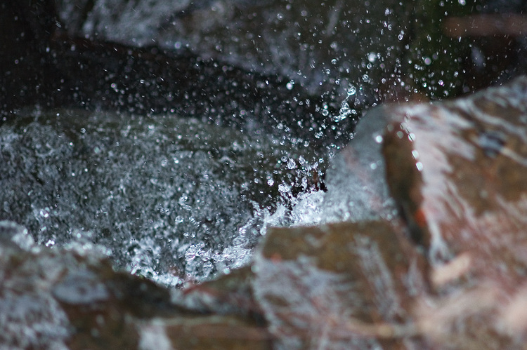 Water drops frozen as they fall over a small waterfall